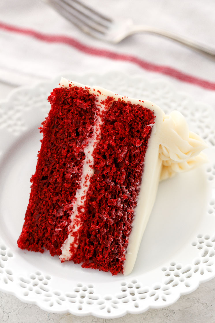 A single slice of red velvet cake on a decorative white plate with a white napkin and fork in the background.
