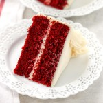 A slice of red velvet cake topped with cream cheese frosting on a white decorative plate.