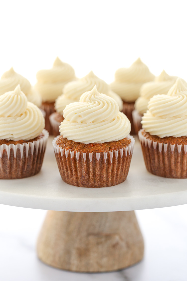 A Group Of Carrot Cake Cupcakes Topped With Cream Cheese Frosting Resting On Top