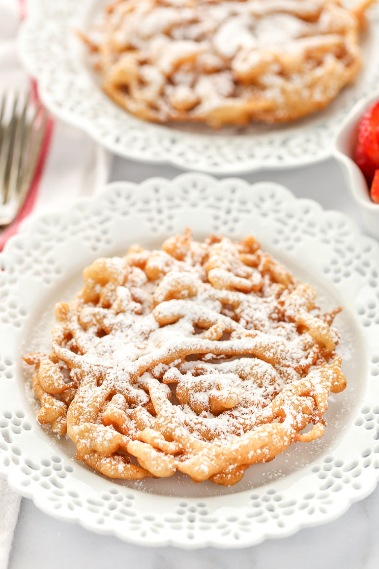 Two homemade funnel cakes topped with powdered sugar on decorative white plates and strawberries on the side.