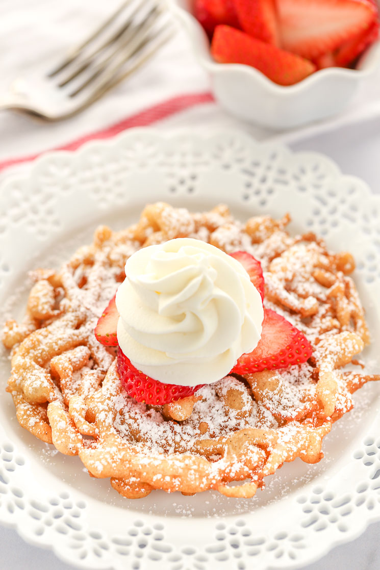 A homemade funnel cake topped with strawberries and homemade whipped cream sitting on a decorative white plate.
