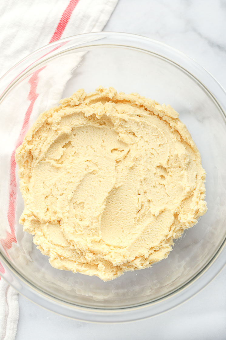 A clear glass mixing bowl filled with shortbread cookie dough and a red and white napkin in the background.