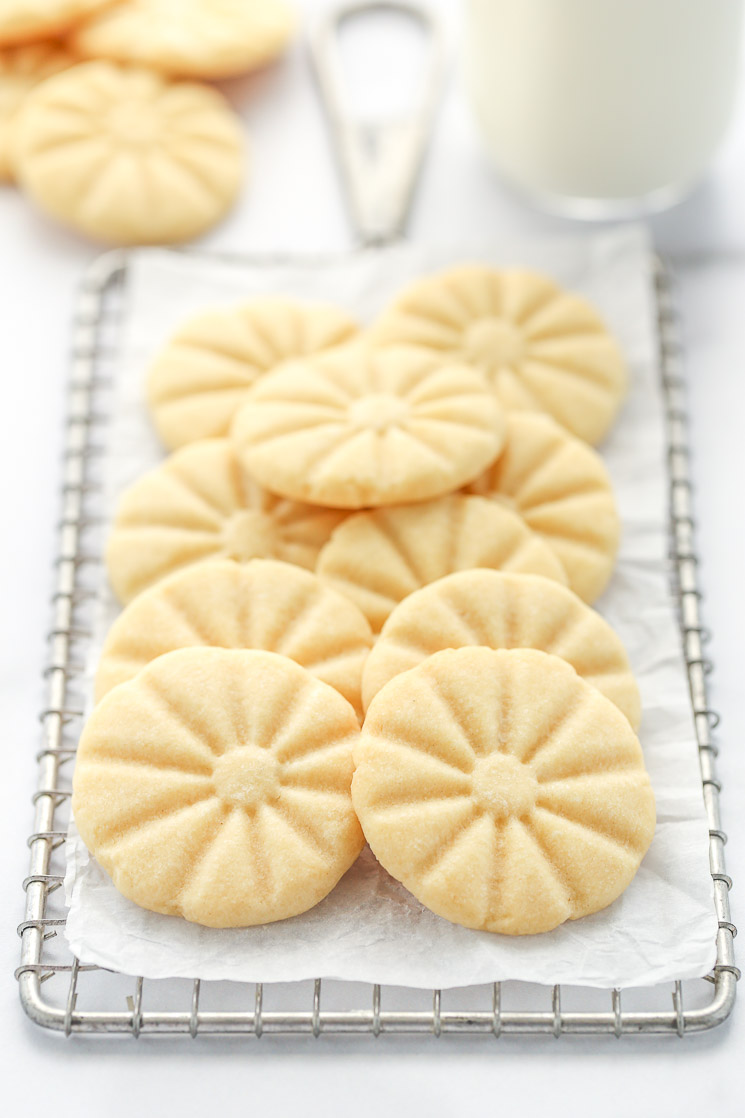 A group of shortbread cookies on top of an antique safety grater with other cookies and milk in the background.