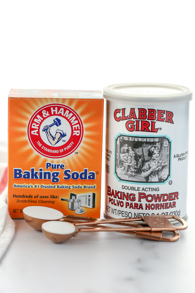 A box of baking soda and can of baking powder on top of a marble surface.
