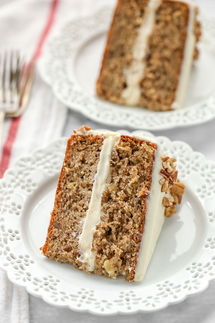 A slice of hummingbird cake on a decorative white plate with another slice and a fork in the background.