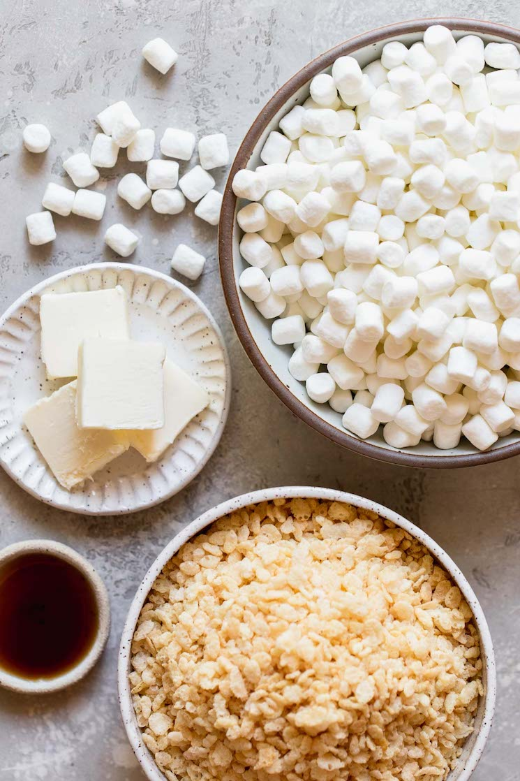 Marshmallows, sliced butter, vanilla extract, and cereal laying out on a gray surface in white and brown plates.