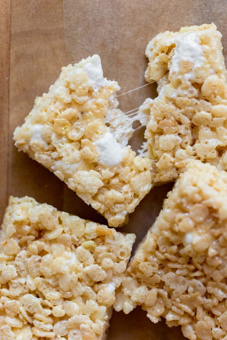 A close up image of a Rice Krispie treat being pulled apart with gooey marshmallow strings between the two halves.