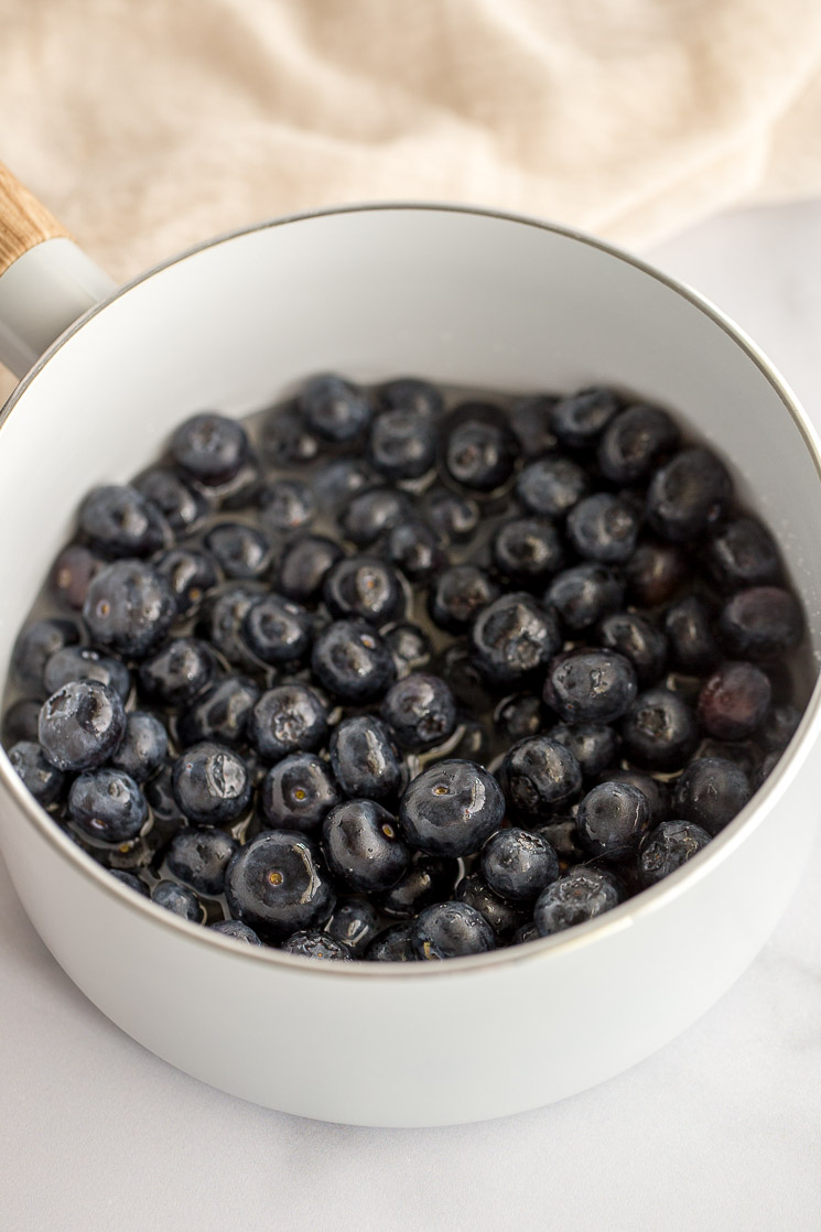 A white saucepan filled with fresh blueberries, water, sugar, and lemon juice.