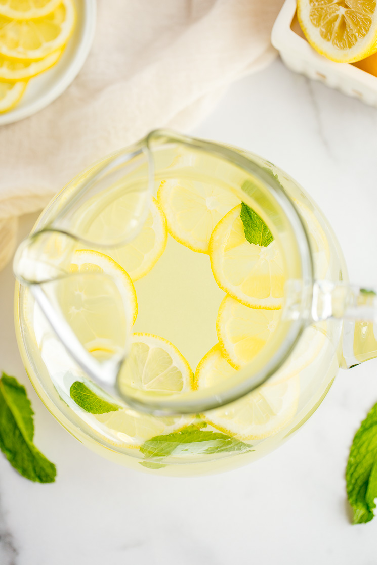A large glass pitcher filled with homemade lemonade, lemon slices, and fresh mint leaves.