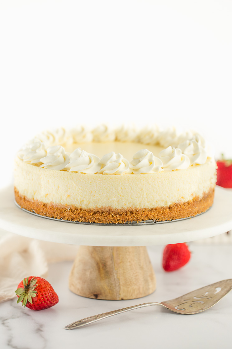 A cheesecake topped with whipped cream on top of a marble cake stand.