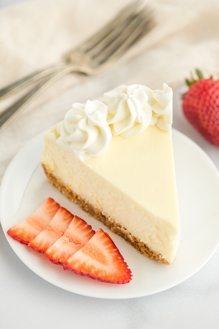 A slice of cheesecake topped with whipped cream on a white plate.