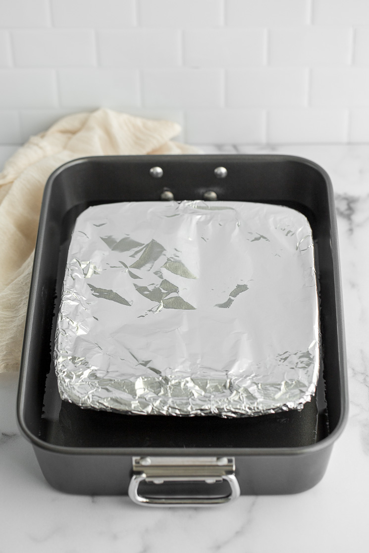 A baking dish with sweetened condensed milk covered in foil inside of a roasting pan.