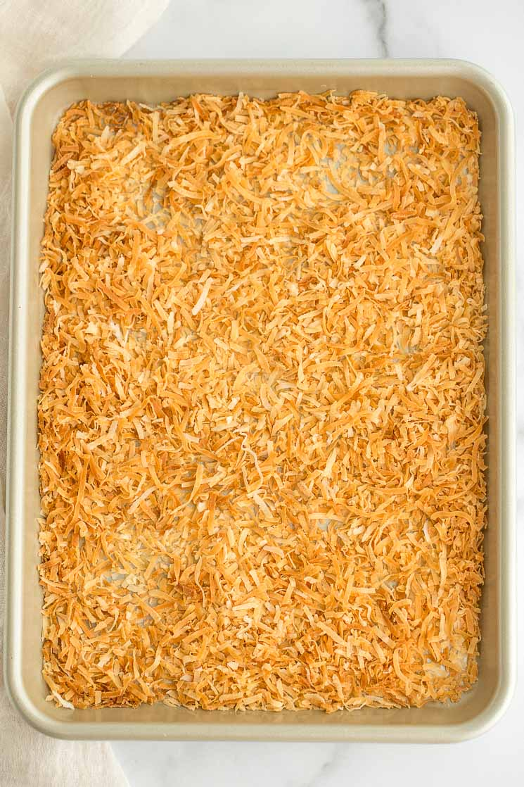 A batch of toasted coconut spread out onto a baking sheet.