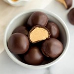 A small white bowl filled with peanut butter balls.