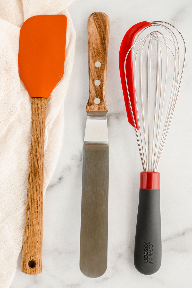 A rubber spatula, an icing spatula, and a whisk resting on top of a marble counter.