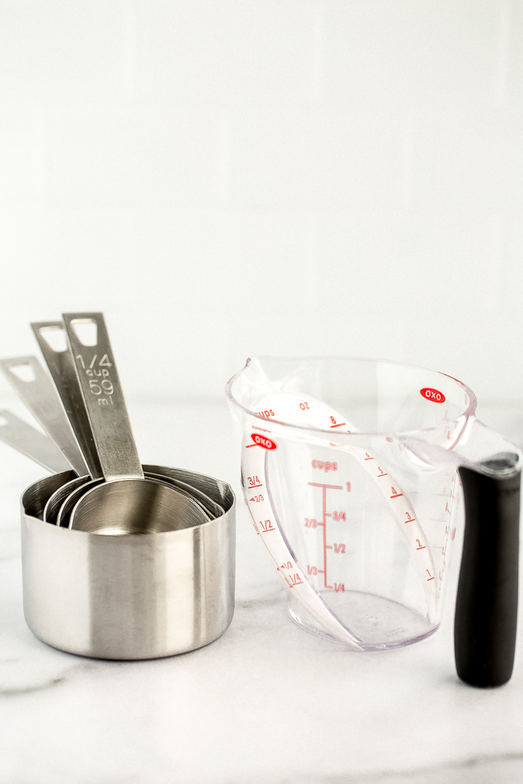 A set of metal measuring cups and a plastic angled liquid measuring cup sitting on a marble counter.