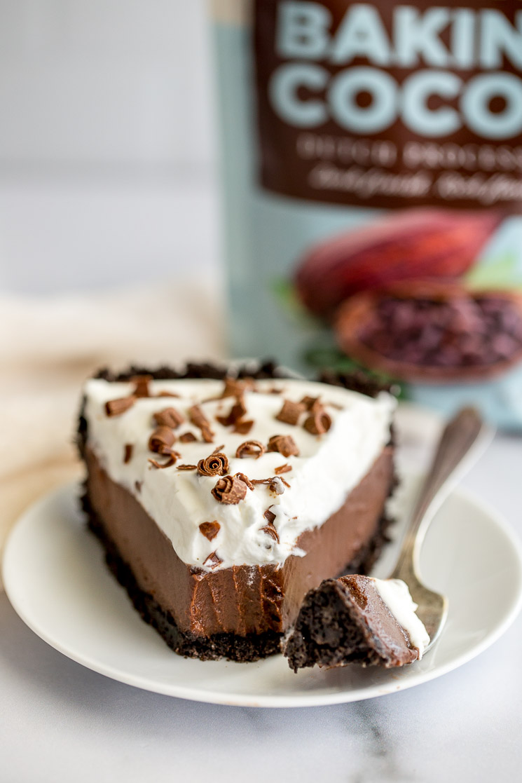 A slice of chocolate cream pie sitting on a white plate.