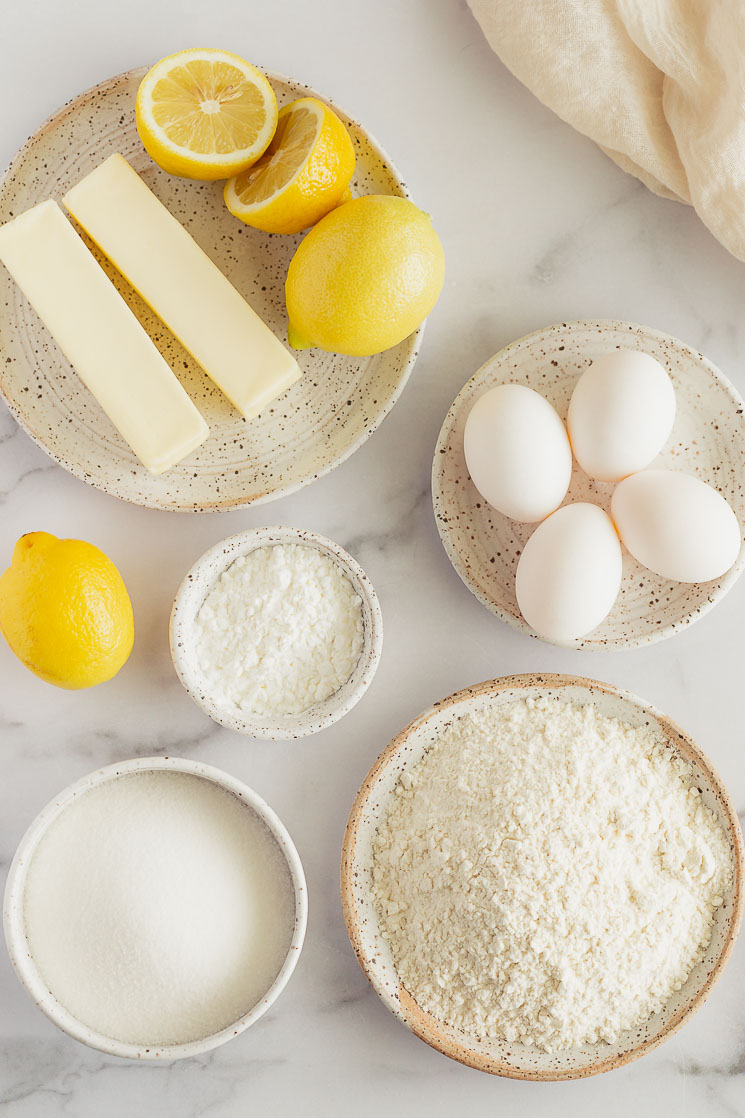 The ingredients for lemon bars in various bowls and plates on top of a marble surface.