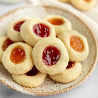 Thumbprint cookies sitting on top of a speckled plate.
