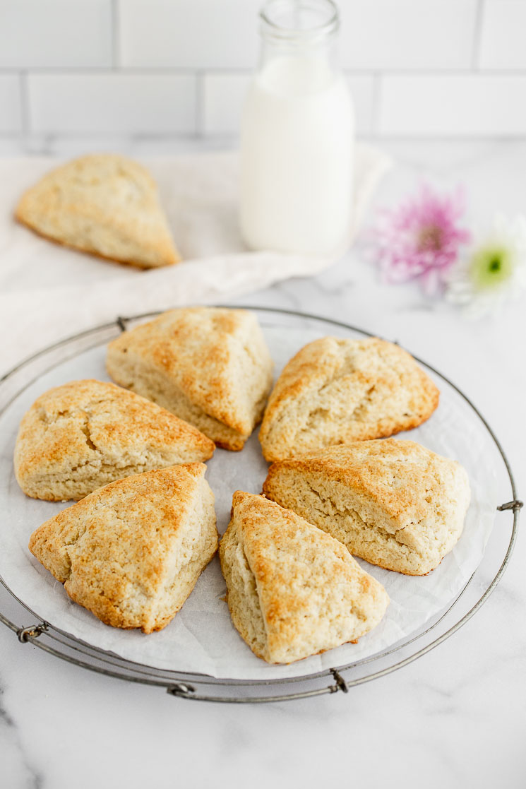 A cooling rack displaying scones in a circle with a glass of milk and flowers in the background.