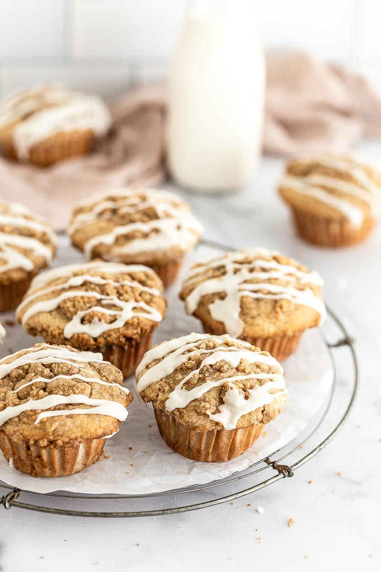 Glazed apple muffins on top of a round wire rack.