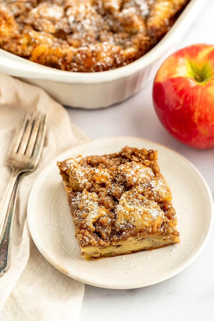 A slice of apple streusel french toast casserole on a white plate.