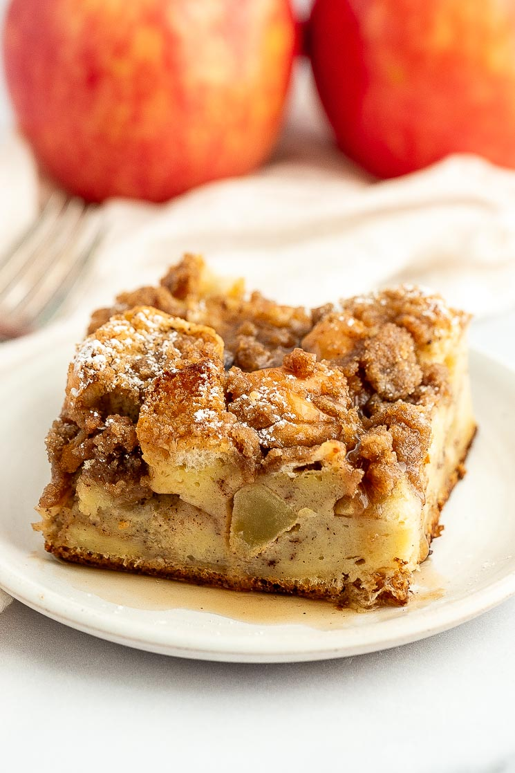 A slice of apple streusel french toast casserole topped with maple syrup on a white plate.