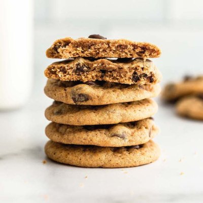 A stack of pumpkin chocolate chip cookies on a marble surface.