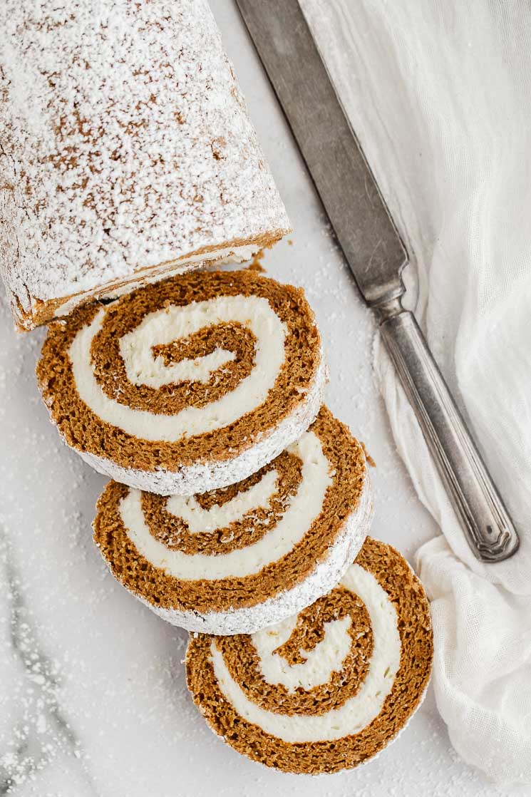 A partially sliced pumpkin roll on a marble surface.