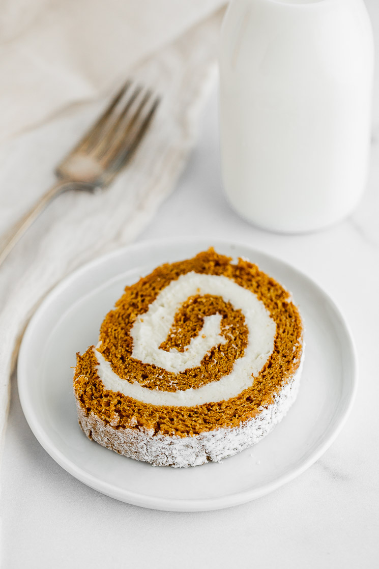 A slice of pumpkin roll on a white plate.