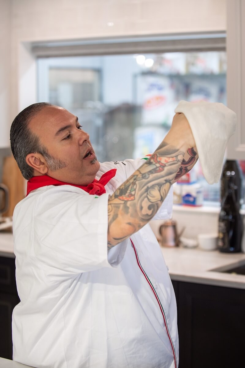 A picture of a chef showing how to stretch pizza dough.