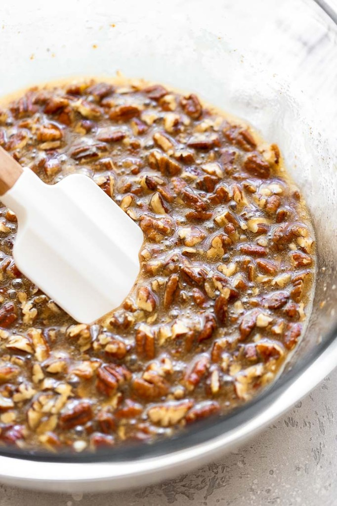 Pecan pie filling in a glass mixing bowl.