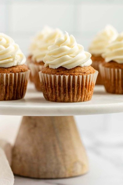 Pumpkin cupcakes sitting on top of a marble cake stand.