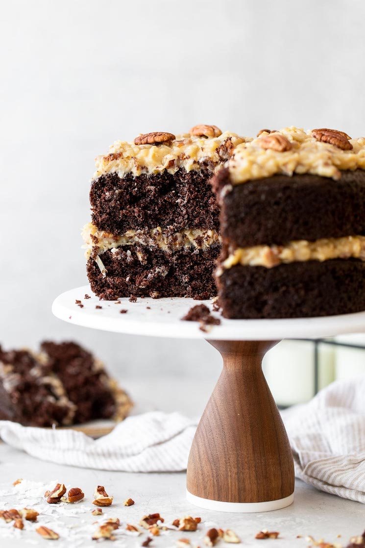 A layered German Chocolate Cake on a marble cake stand with a slice taken out to show the layers more clearly.