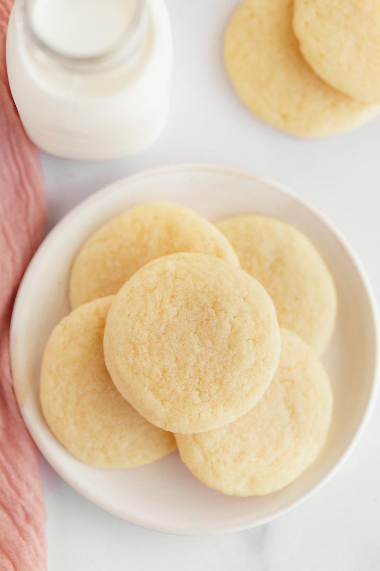 Um prato branco com biscoitos de açúcar e mais biscoitos e um jarro de leite no fundo.