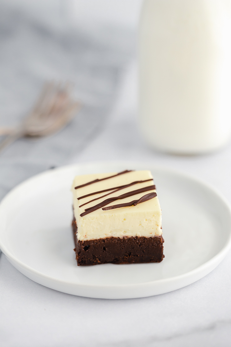 An individual cheesecake brownie drizzled with chocolate on a white plate with forks and milk in the background.