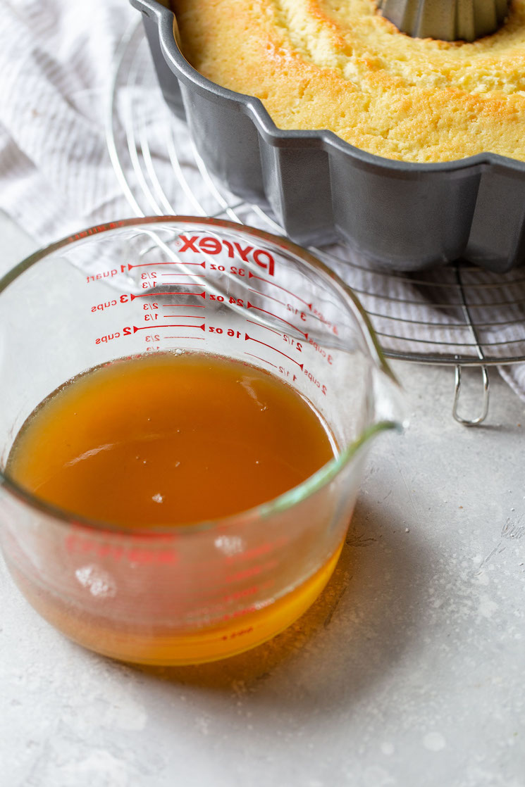 A glass measuring cup holding the rum syrup.