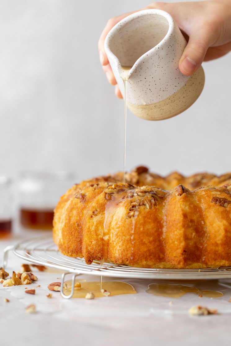 A baked rum cake resting on a round cooling rack and the rum glaze being poured over the top.