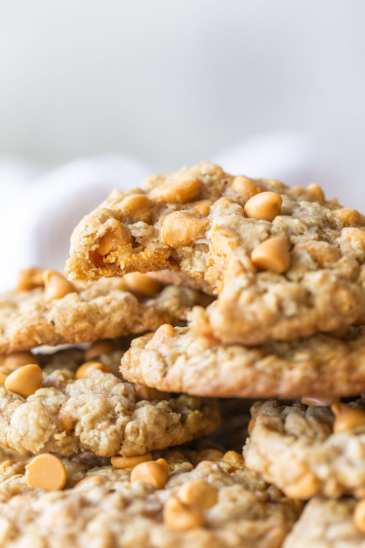 A stack of oatmeal scotchies with one having a bite taken out to see the inside detail of the cookie.
