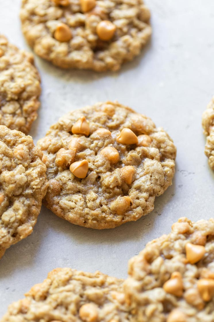 Baked oatmeal scotchies scattered on a rustic gray surface.