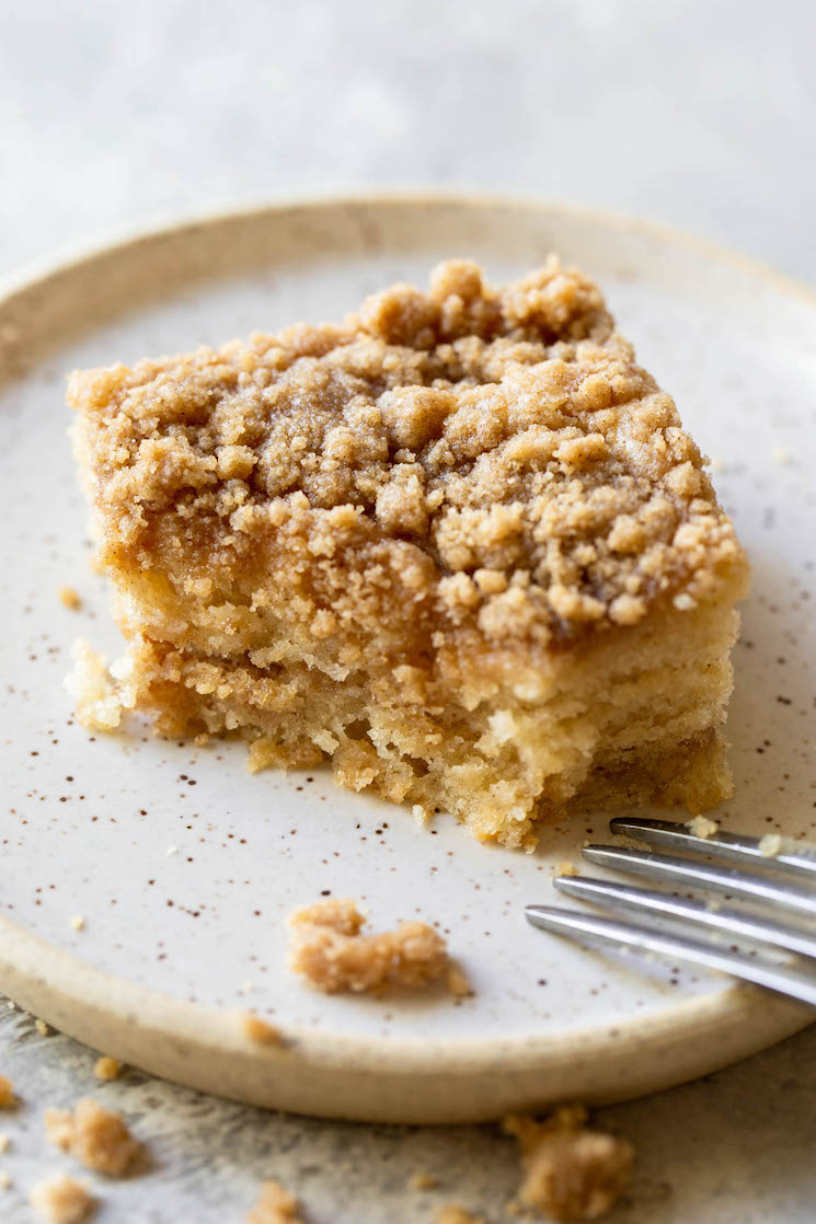 A single piece of coffee cake resting on a rustic plate with a bite taken out of the corner.