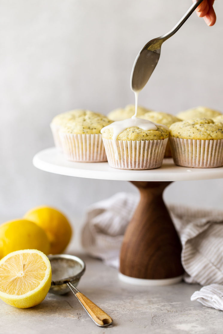 A marble cake stand with lemon poppy seed muffins being topped with an easy lemon glaze.