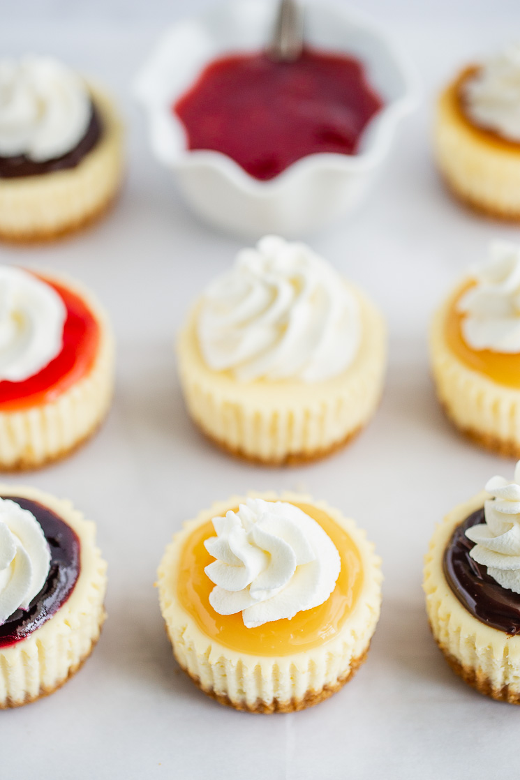 A piece of parchment paper lined with mini cheesecakes topped with different toppings and whipped cream.