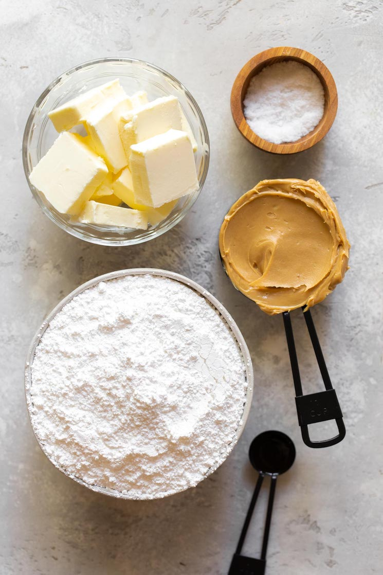 The ingredients needed to make peanut butter fudge laid out on a rustic gray surface.