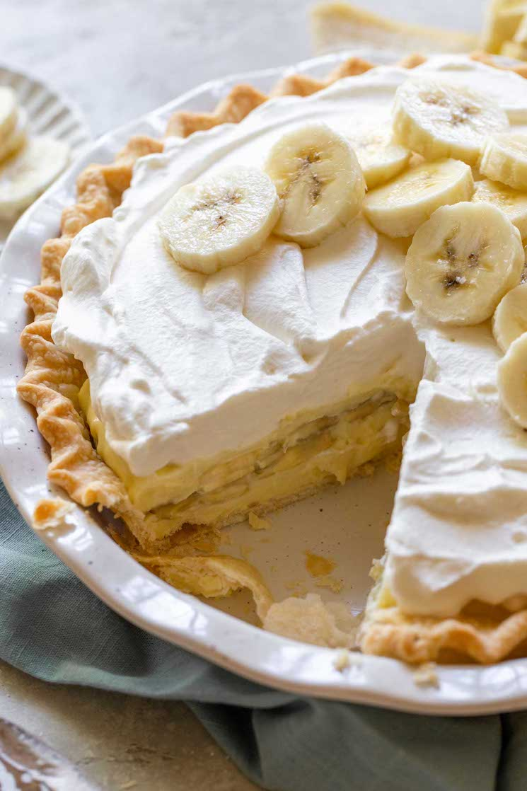 A finished banana cream pie with one slice cut out to show the layers of filling, bananas, and homemade whipped cream.