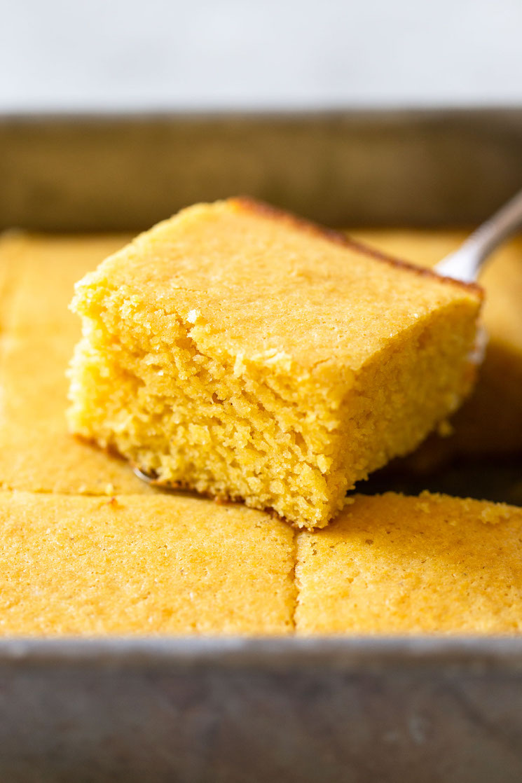 A finished pan of cornbread with one piece cut out and sitting on top showing the texture and golden color.