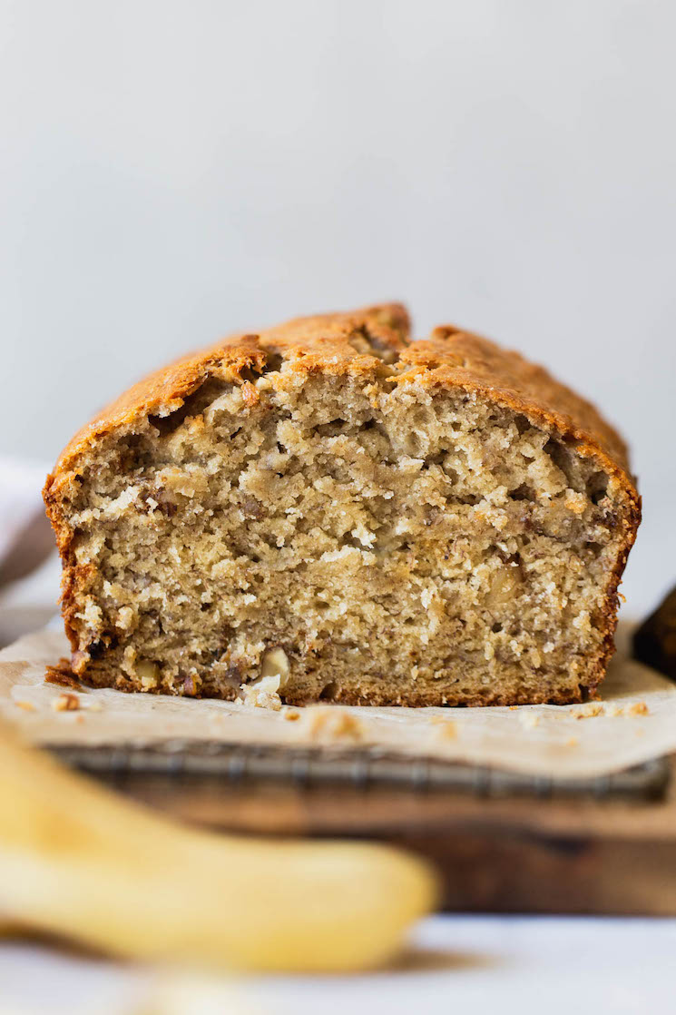 A straight on shot of a loaf of banana bread with the end cut off to show the texture.