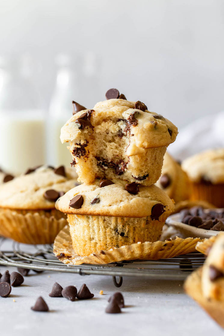 Two muffins stacked on top of each other with one having a bite taken out to show the texture of the muffin.