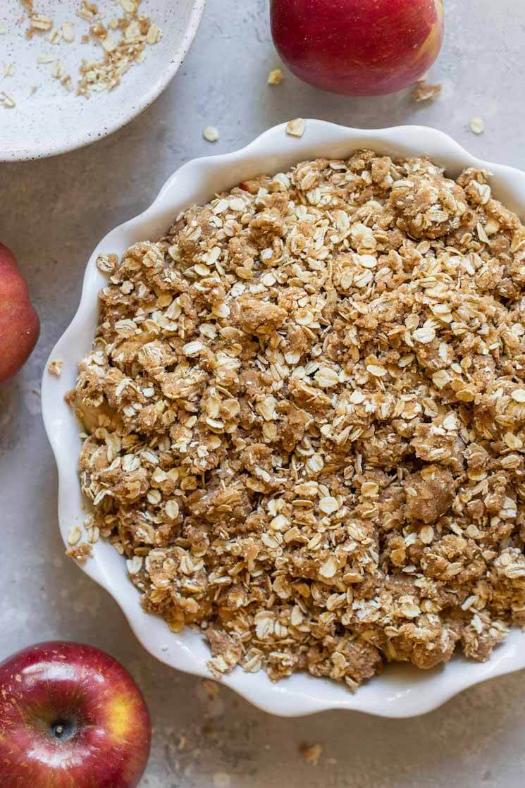 An apple crisp ready to go in the oven surrounded by more apples.