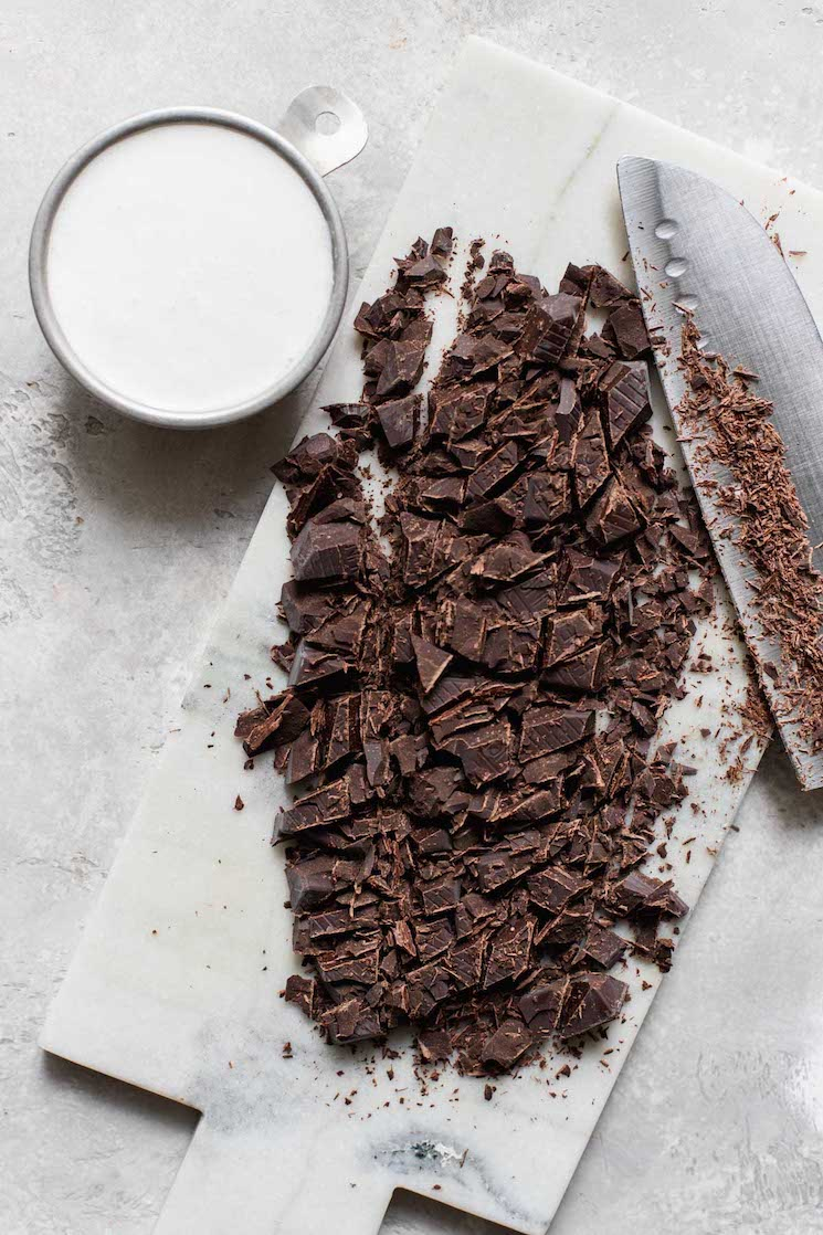 A marble cutting board covered with chopped chocolate and a small cup filled with heavy cream beside it.